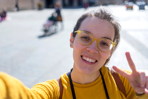 Portrait of smiling female tourist gesturing peace sign in city during sunny dayの写真素材 [FYI03752023]