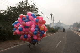 Colorful balls tied to bicycle on road against clear skyの写真素材 [FYI03752209]