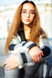 Portrait of serious woman wearing eyeglasses while sitting against buildingの写真素材 [FYI03752238]
