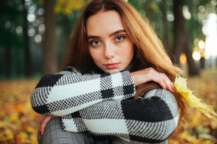 Close-up portrait of serious woman with brown hair siting in park during autumnの写真素材 [FYI03752240]