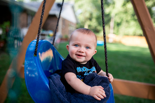 Portrait of cute baby boy sitting in swing at backyardの写真素材 [FYI03752295]