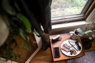 High angle view of accessories in plate on table by window at homeの写真素材 [FYI03752555]