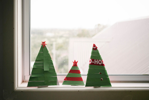 Close-up of paper Christmas trees on window sill at homeの写真素材 [FYI03752586]