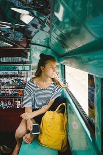 Female tourist with backpack looking through window while travelling in motor homeの写真素材 [FYI03752619]