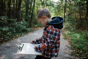 Side view of boy writing in paper on clipboard while standing at forestの写真素材 [FYI03752767]