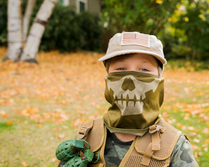 Portrait of cute boy wearing army soldier costume while standing on grassy field in parkの写真素材 [FYI03752831]