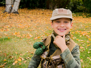 Portrait of cute smiling boy wearing army soldier costume while sitting on grassy field in parkの写真素材 [FYI03752833]