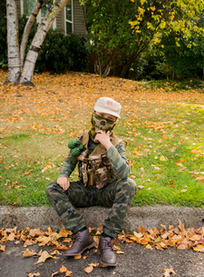 Portrait of boy wearing army soldier costume while sitting on grassy field in parkの写真素材 [FYI03752837]