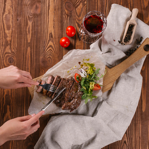 Cropped hands of woman cutting beef steak with cutlery on tableの写真素材 [FYI03752943]