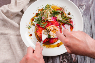 Cropped hands of man having savory crepes with salmon and poached egg in plate on tableの写真素材 [FYI03752972]