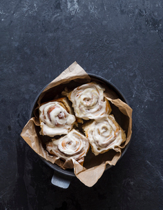 High angle view of cinnamon buns with cream in bowl on tableの写真素材 [FYI03753326]