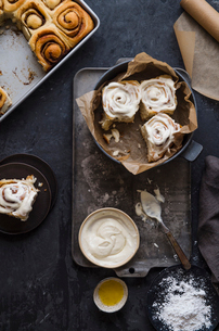 High angle view of cinnamon buns with cream and flour on tableの写真素材 [FYI03753330]