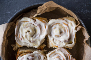 Overhead view of cinnamon buns with cream in bowl on tableの写真素材 [FYI03753332]