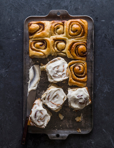 High angle view of cinnamon buns with cream in baking sheet on tableの写真素材 [FYI03753342]
