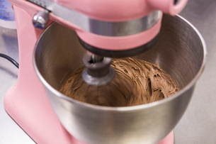 High angle close-up of chocolate batter mixing in mixer on kitchen counter at laboratoryの写真素材 [FYI03753486]