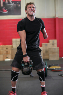 Full length of aggressive male adaptive athlete lifting kettlebell while standing against wall in gyの写真素材 [FYI03753545]