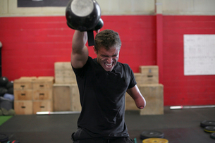 Aggressive male adaptive athlete lifting kettlebell while standing against wall in gymの写真素材 [FYI03753549]