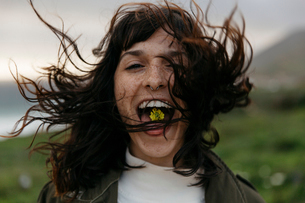 Close-up portrait of woman with flower in mouth standing against sky during sunsetの写真素材 [FYI03753577]