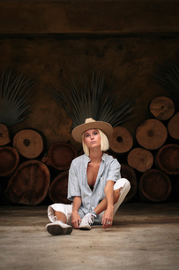 Portrait of confident woman wearing beige hat while sitting on floor against decorated wallの写真素材 [FYI03753640]