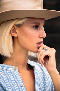 Close-up of thoughtful woman wearing beige hat while standing outdoorsの写真素材 [FYI03753642]