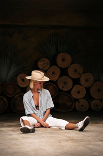 Confident woman with legs apart wearing beige hat while sitting on floor against decorated wallの写真素材 [FYI03753643]