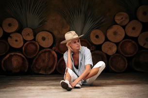 Confident woman wearing beige hat while sitting on floor against decorated wallの写真素材 [FYI03753645]