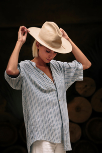 Confident woman wearing beige hat while standing against decorated wallの写真素材 [FYI03753648]