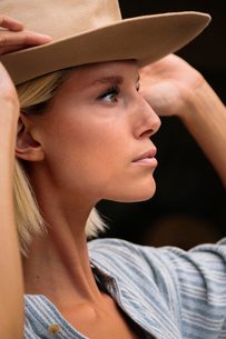 Close-up of thoughtful woman wearing beige hat looking away while standing outdoorsの写真素材 [FYI03753650]