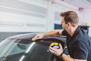 Side view of male worker polishing car roof in workshopの写真素材 [FYI03753706]