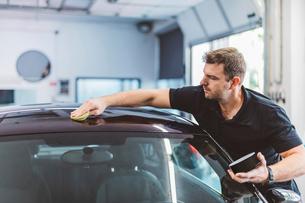 Male worker polishing car roof in workshopの写真素材 [FYI03753709]