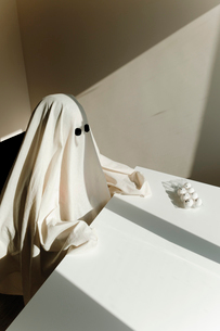 High angle view of man in ghost costume sitting by table at home during Halloweenの写真素材 [FYI03753720]
