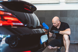 Male worker cleaning car with towel while crouching in workshopの写真素材 [FYI03753721]