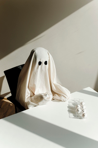 High angle view of man in ghost costume with egg carton on table sitting at home during Halloweenの写真素材 [FYI03753726]