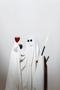 Man in ghost costume holding sparkler and wineglass while standing against wallの写真素材 [FYI03753727]