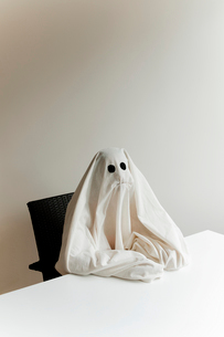 Man in ghost costume sitting by table against wall at home during Halloweenの写真素材 [FYI03753728]