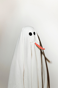 Man in ghost costume blowing party horn blower while standing against wallの写真素材 [FYI03753729]