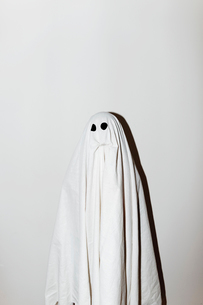 Man in ghost costume standing against wallの写真素材 [FYI03753730]