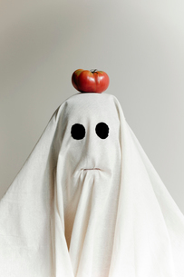 Man in ghost costume carrying squash on head while standing against wallの写真素材 [FYI03753731]