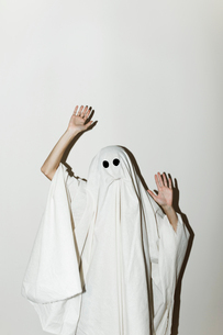 Man in ghost costume gesturing while standing against wallの写真素材 [FYI03753734]