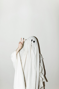 Man in ghost costume showing peace sign while standing against wallの写真素材 [FYI03753735]