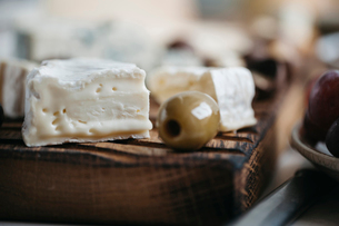 Close-up of cheese with green olive on wooden tableの写真素材 [FYI03754535]