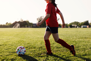 Side view of girl playing soccer on field against sky during sunny dayの写真素材 [FYI03754756]