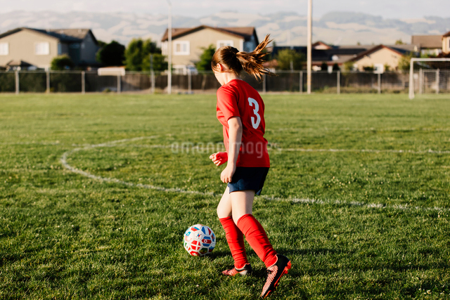 Full length of girl wearing uniform playing soccer on fieldの写真素材 [FYI03754761]