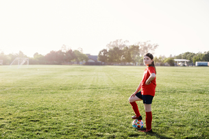 Side view portrait of confident girl with soccer ball standing on playing field against sky during sの写真素材 [FYI03754764]