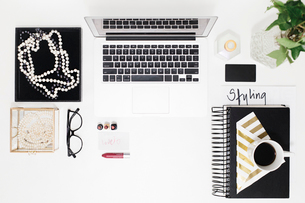Overhead view of personal accessories with office supplies arranged on desk in officeの写真素材 [FYI03754795]