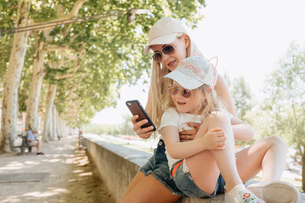 Mother using smart phone while sitting with daughter on retaining wall in parkの写真素材 [FYI03755013]