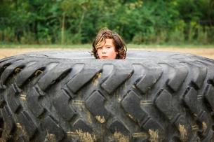 Portrait of cute boy peeking through dirty tire against plantsの写真素材 [FYI03755240]