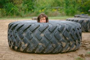 Portrait of cute boy peeking through dirty tireの写真素材 [FYI03755244]
