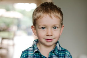 Close-up portrait of cute smiling boy at homeの写真素材 [FYI03755443]