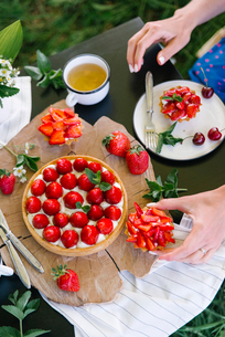 Cropped hands of woman eating strawberry cake on table in yardの写真素材 [FYI03755545]